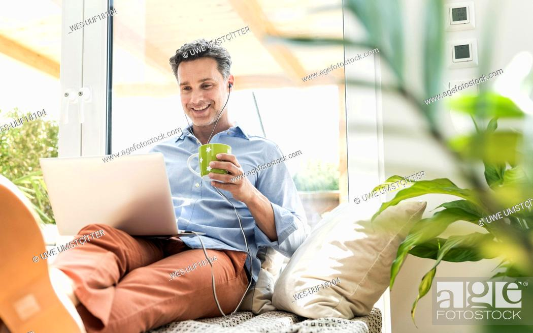 Stock Photo: Mature man sitting on couch, using laptop, drinking coffee.