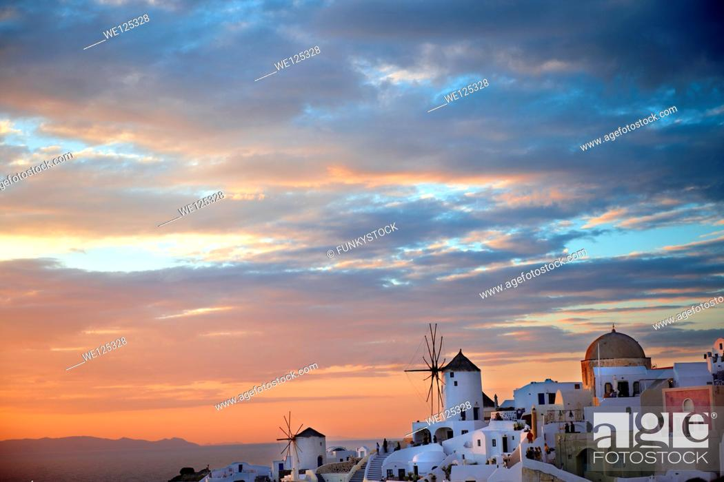 Stock Photo: Oia Ia Santorini - Windmills and town at sunset, Greek Cyclades islands.