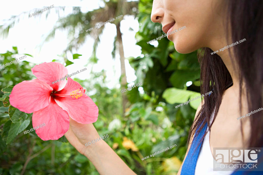 Stock Photo: Woman holding pink flower.