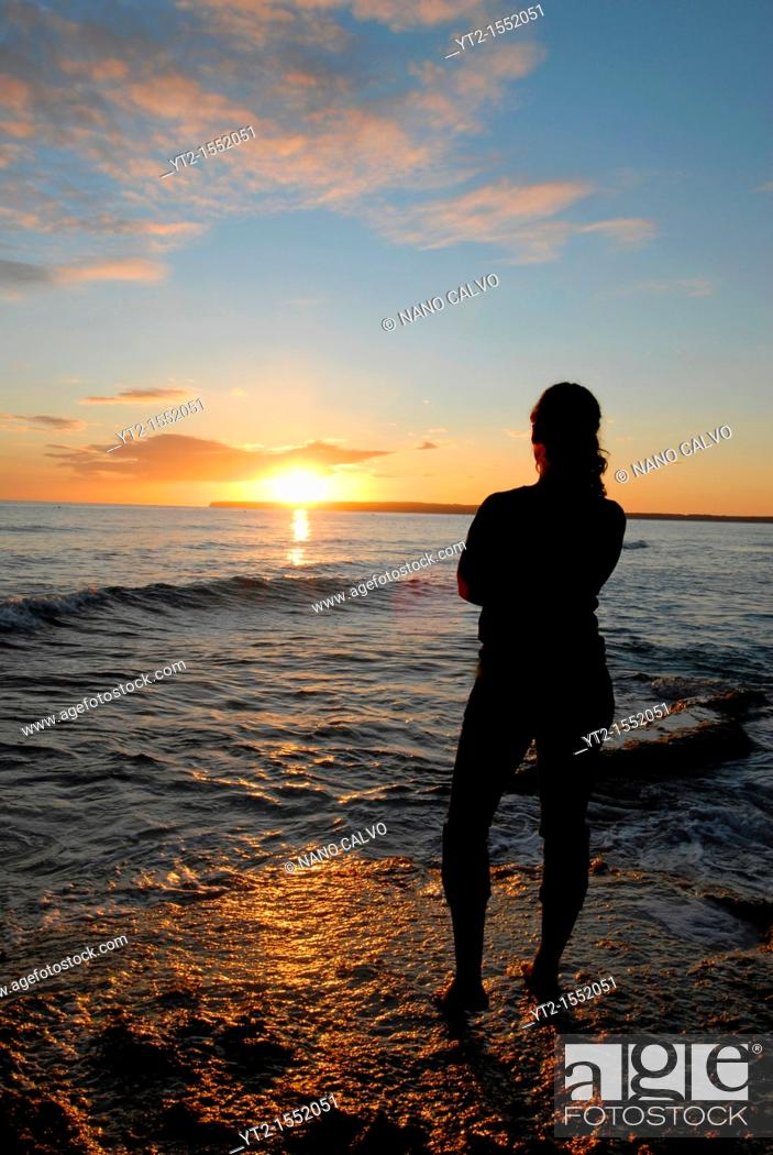 Stock Photo: Young woman enjoying a beautiful sunset at Migjorn beach, Formentera.