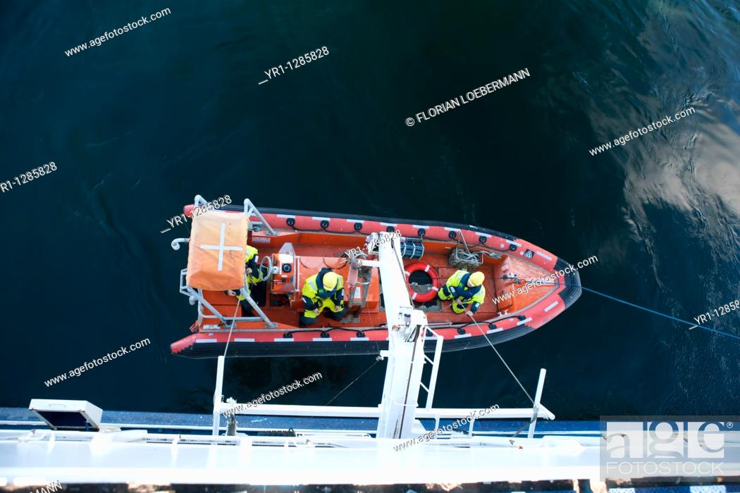 Stock Photo: A life boat is launched to rescue a man over board.