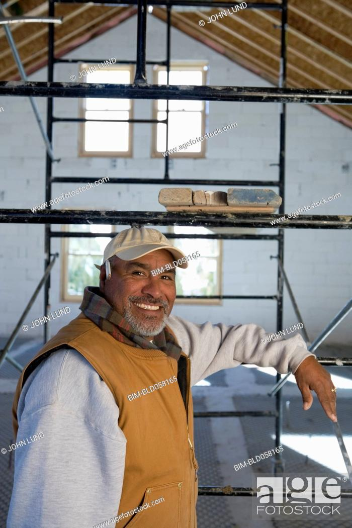 Stock Photo: Hispanic man leaning on scaffolding.