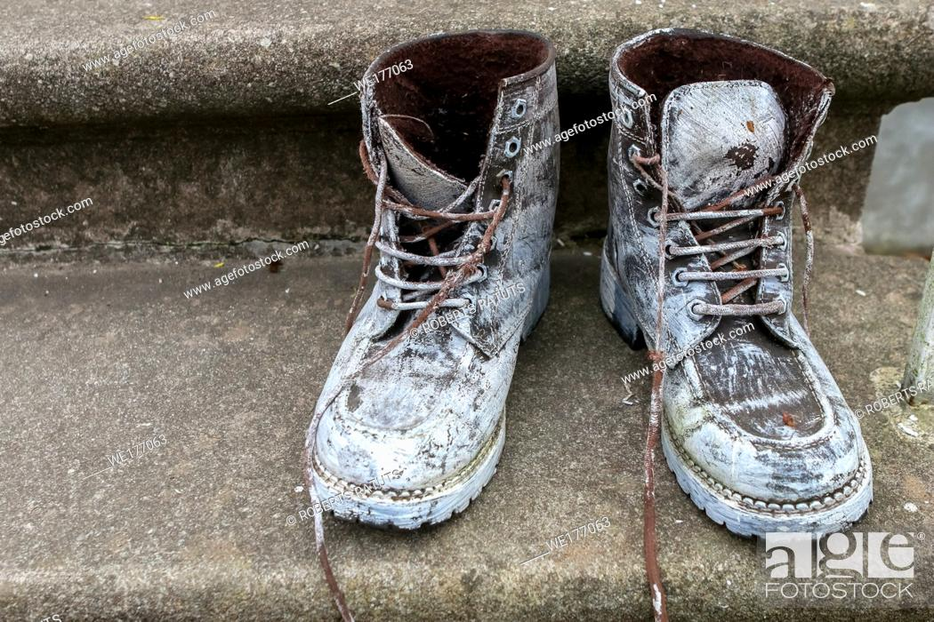 Imagen: Old brown work boots. Boots smeared with white paint. Dirty boots on the stairs. Dirty old workboots on stairs.