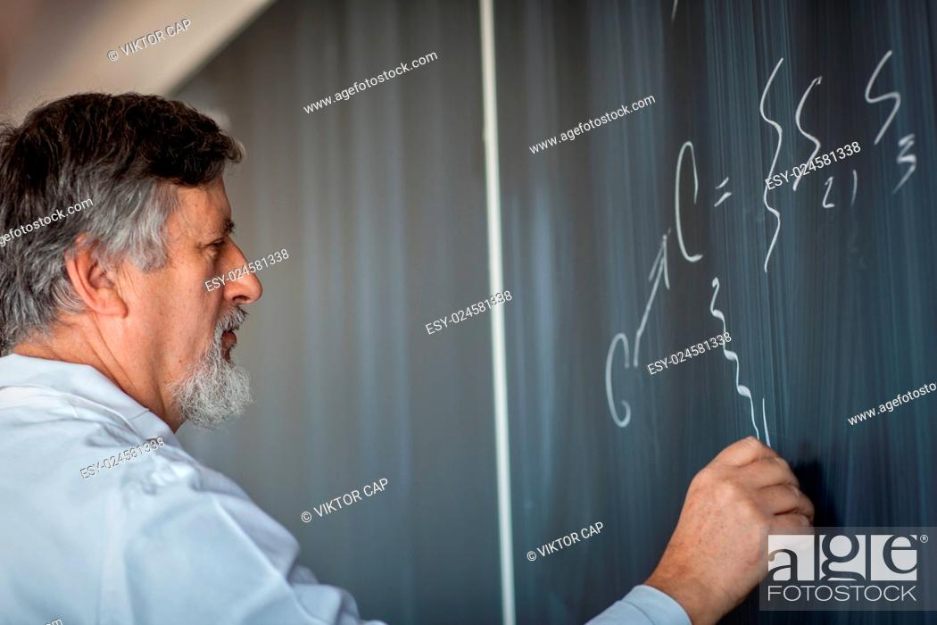 Stock Photo: Senior chemistry professor writing on the board while having a chalk and blackboard lecture (shallow DOF color toned image).