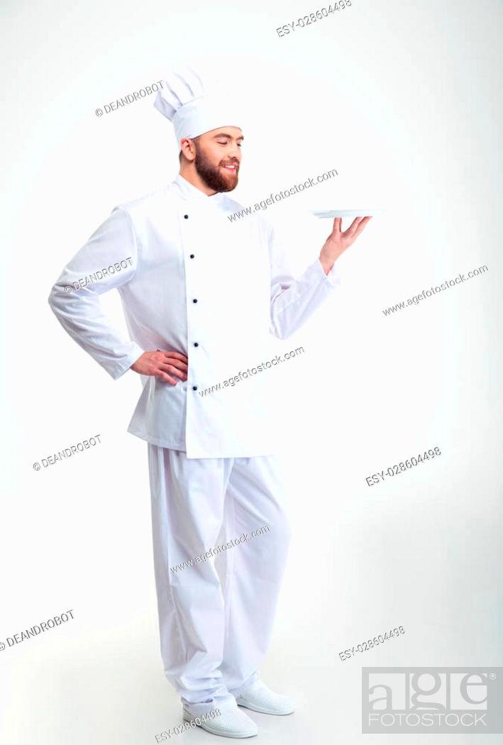 Photo de stock: Portrait of a happy male chef cook standing with plate isolated on a white backgorund.
