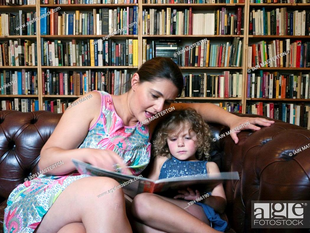 Stock Photo: Woman reading to young girl in a bookshop in Berlin.