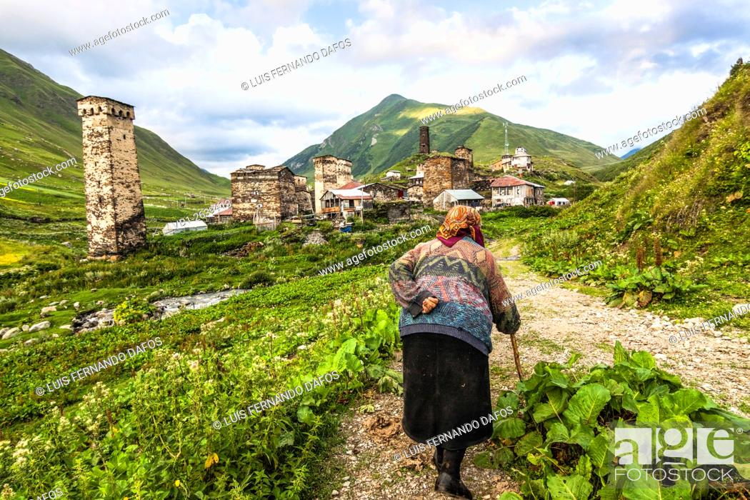 Stock Photo: Old woman walking next to the koshki medieval towers of Ushguli, Georgia, the highest permanently inhabited village in Europe.