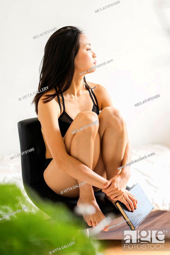 Stock Photo: Attractive young woman in lingerie sitting on chair at home with book.