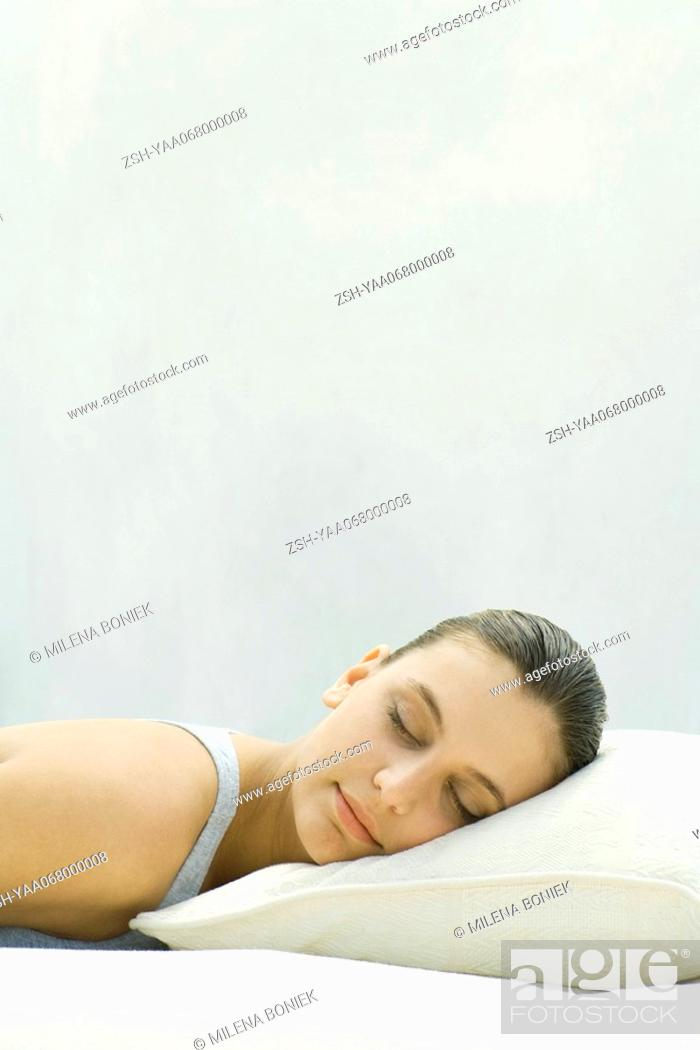 Stock Photo: Woman resting head on pillow, eyes closed.