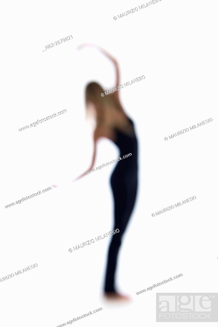 Stock Photo: Blurred silhouette of a woman, she dances on a white backdrop.