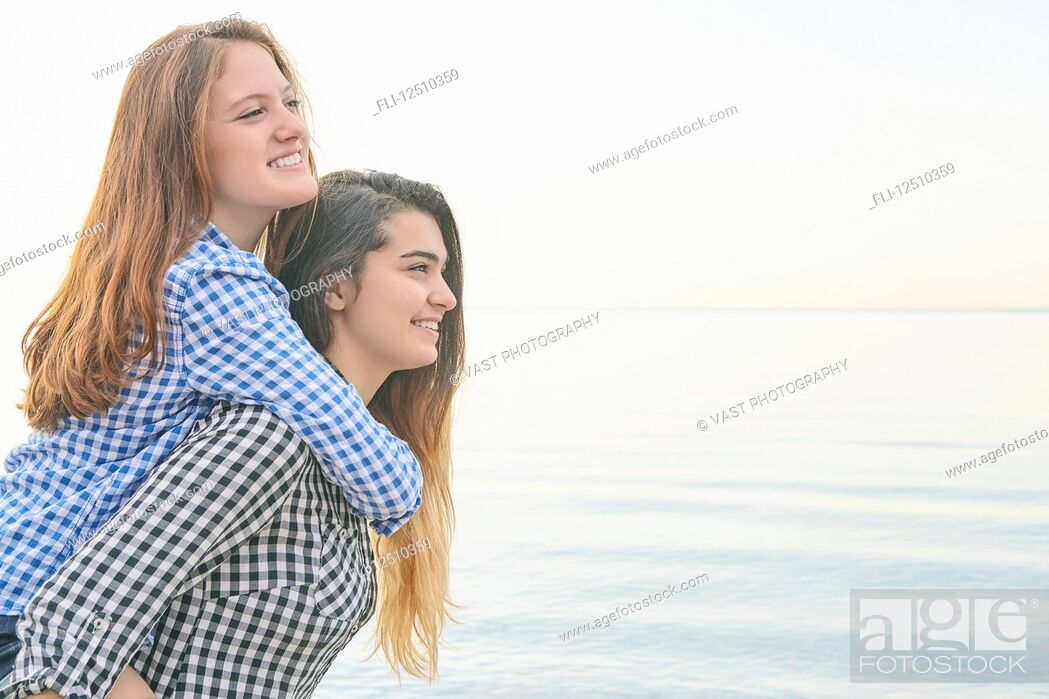 Stock Photo: Side view of two teenage girls at the water's edge, one giving a ride to her friend on her back, Woodbine Beach; Toronto, Ontario, Canada.