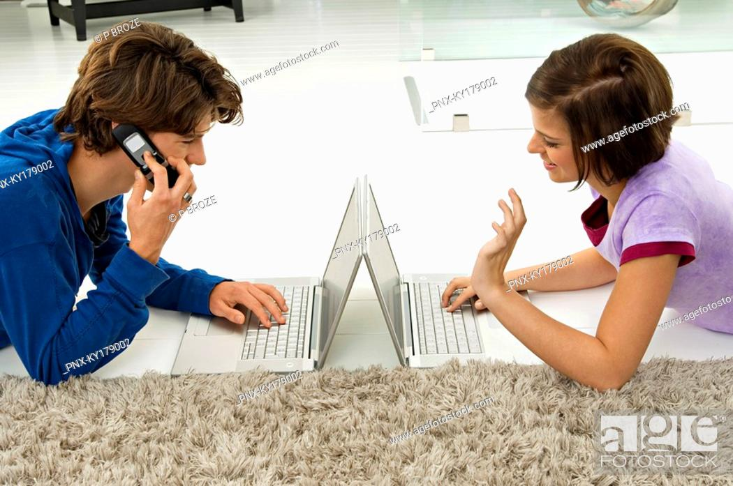 Stock Photo: Teenage boy and a young woman using laptops.