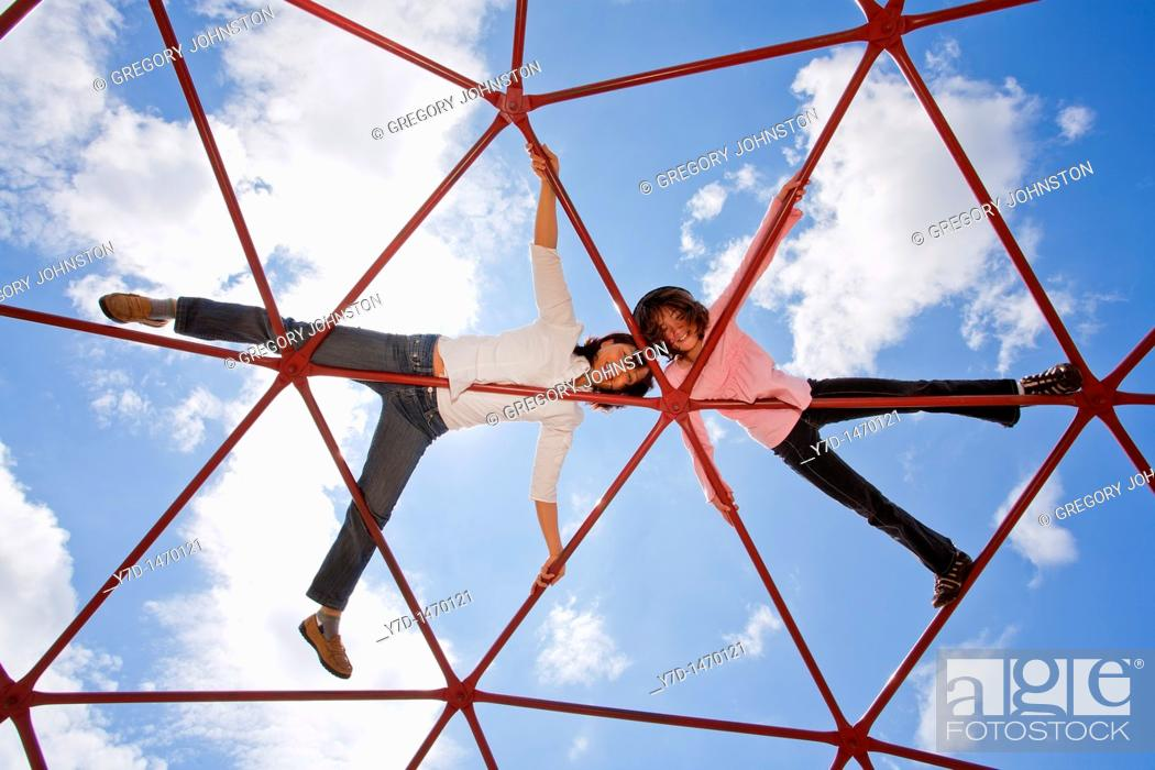 Stock Photo: Mother and her daughter up high on the piece of playground equipment.