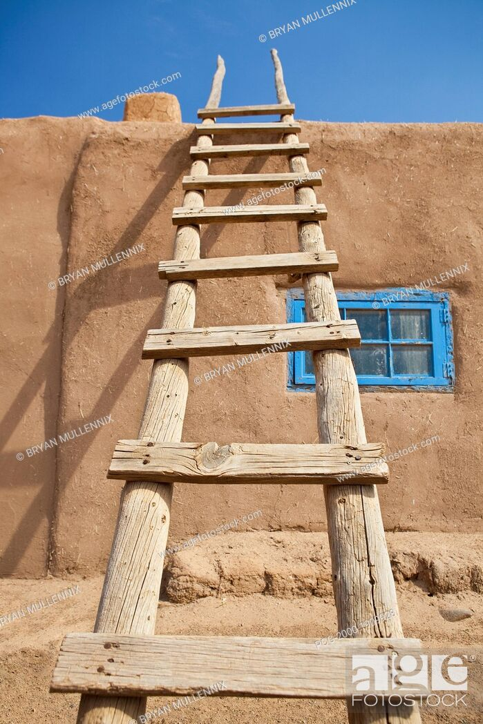 Stock Photo: Wooden Ladder Against an Adobe Building.