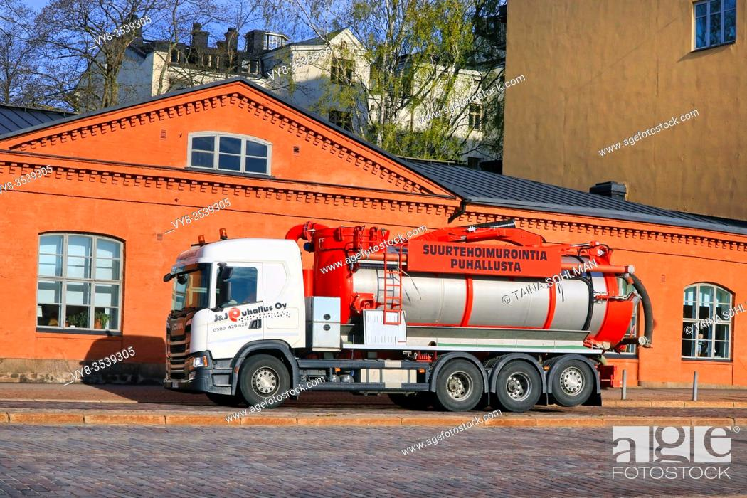Stock Photo: White Scania vacuum and pressure tank truck of J&J Puhallus Oy driving on street in city traffic in morning light. Helsinki, Finland. May 6, 2020.