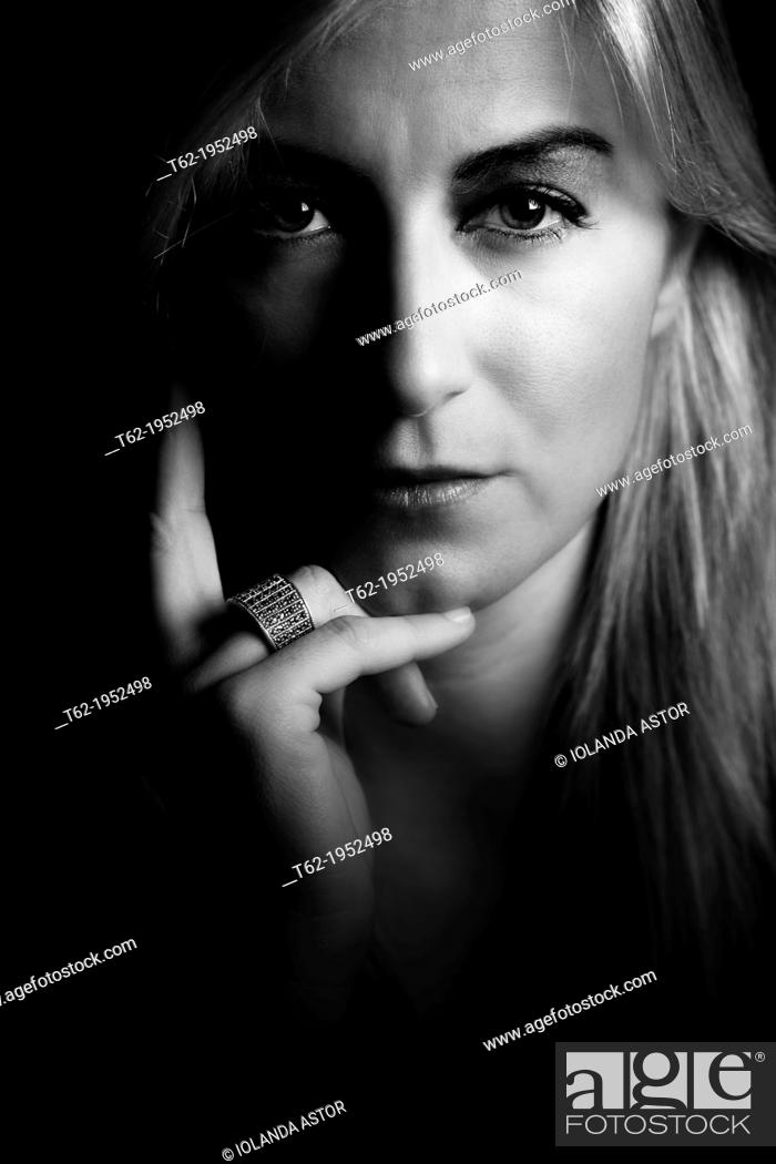 Stock Photo: Face portrait of a beautiful young blonde staring at camera in black and white.
