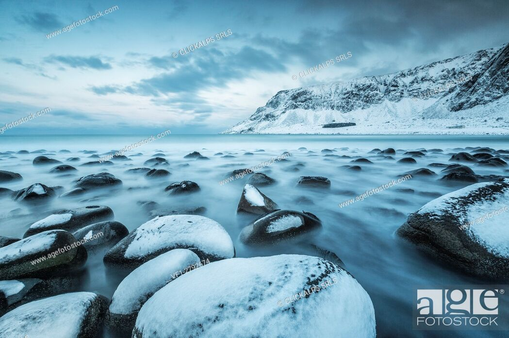 Stock Photo: Rocks in the cold sea and snow capped mountains under the blue light of dusk Unstad Lofoten Islands Northern Norway Europe.