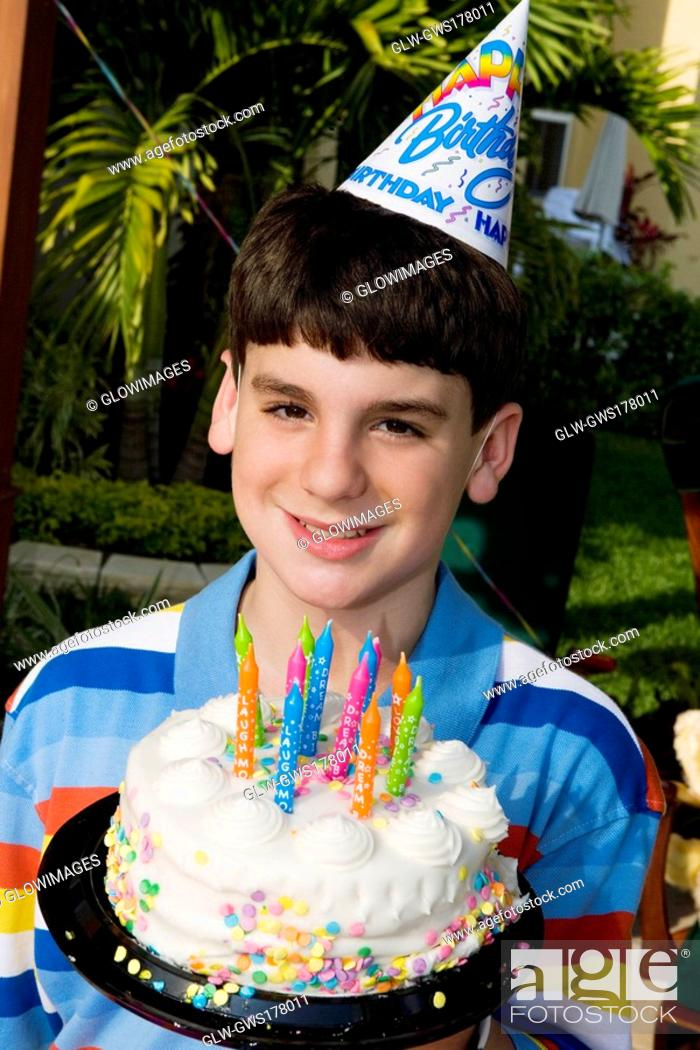 Stock Photo: Portrait of a boy holding a birthday cake and smiling.