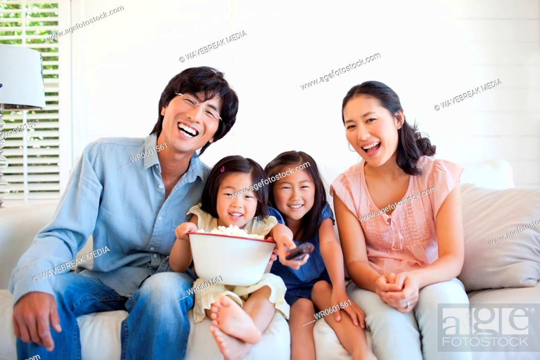 Stock Photo: Family sitting together watching a funny show on the couch.