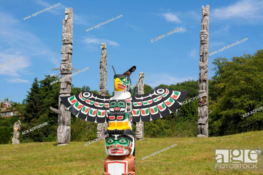 Stock Photo: Thunderbird and Man holding copper by Bruce Alfred, older poles behind, at Namgis Burial grounds, Alert Bay, Cormorant Island, Vancouver Island.