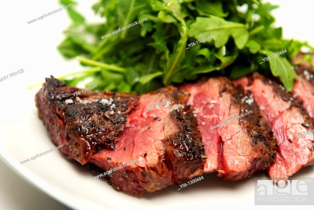 Stock Photo: Rare Sliced Steak and Arugula on a White Plate.