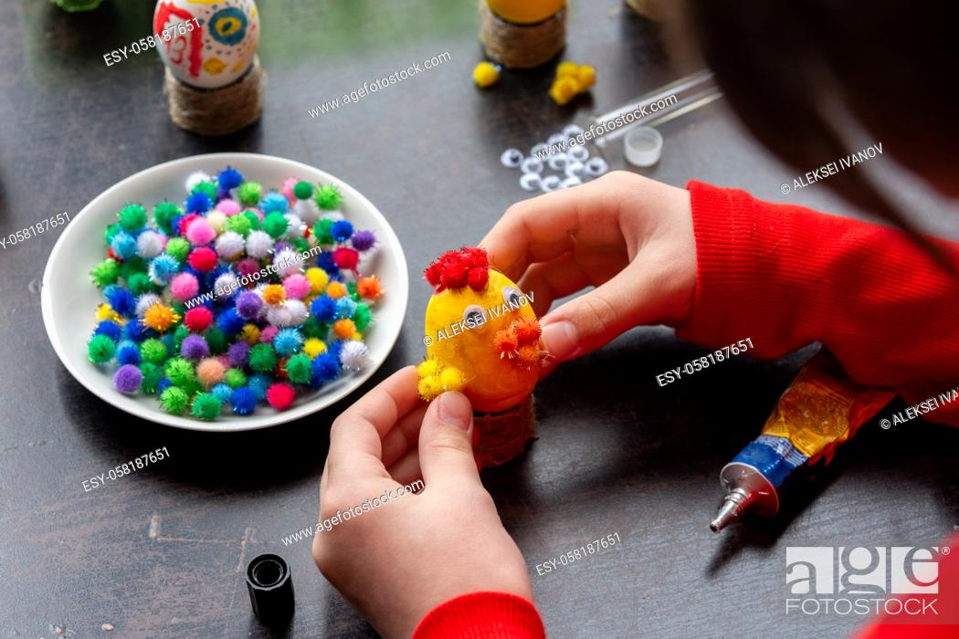 Stock Photo: A girl glues wings to a chicken figurine made from an egg.