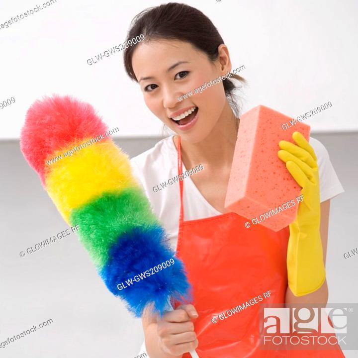 Stock Photo: Young woman holding a duster and a bath sponge.