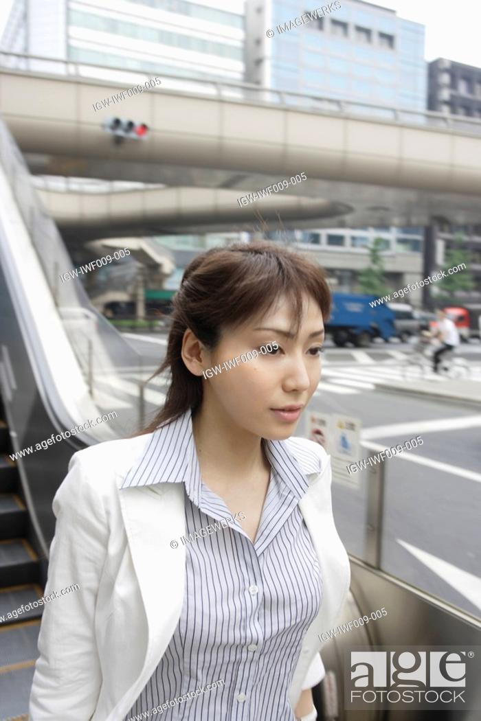 Stock Photo: A woman seen near the railing of the escalators.