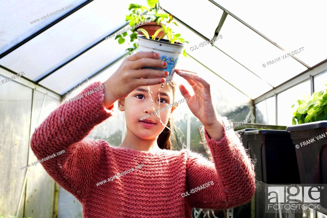 Stock Photo: Girl holding plant pot, looking at roots.