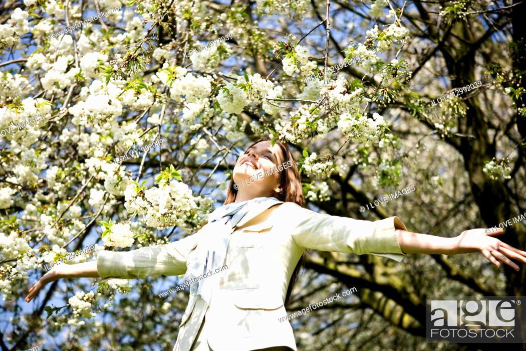Stock Photo: A young woman standing under a tree, arms outstretched.