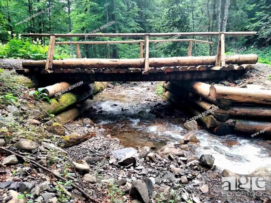 Stock Photo: Mountain river flowing under the wood bridge nature.