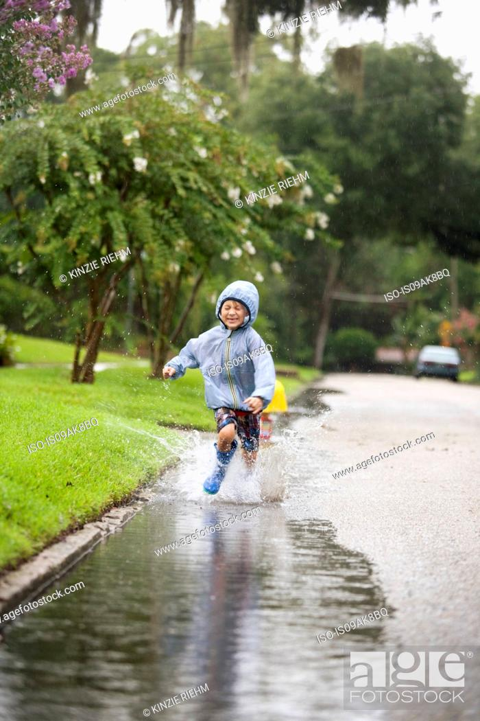 Stock Photo: Boy in rubber boots running and splashing in rain puddle.