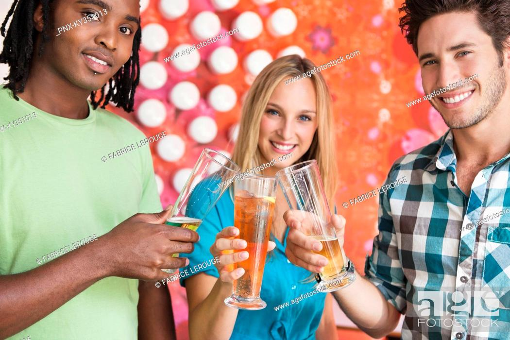 Stock Photo: Portrait of friends toasting drinks at a bar.