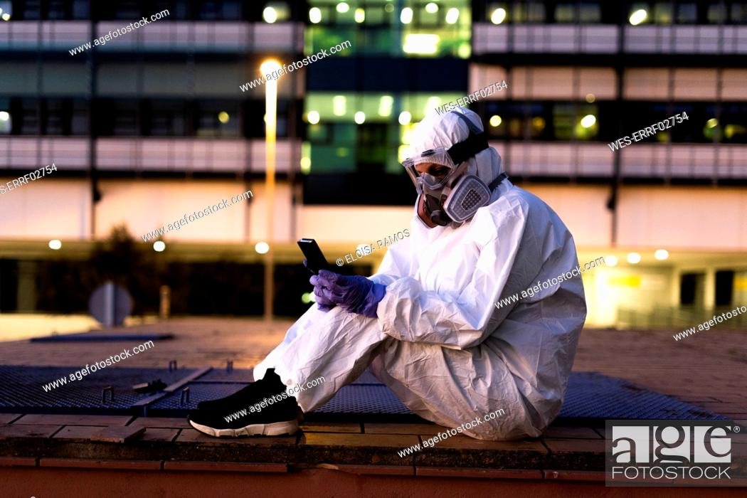 Imagen: Female scientist wearing protective suit and mask using smartphone in front of a laboratory.