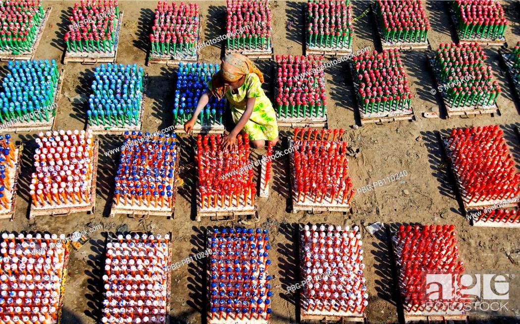 Stock Photo: A girl child works at balloon factory at Kamrangir chor Dhaka, Bangladesh February 2010.