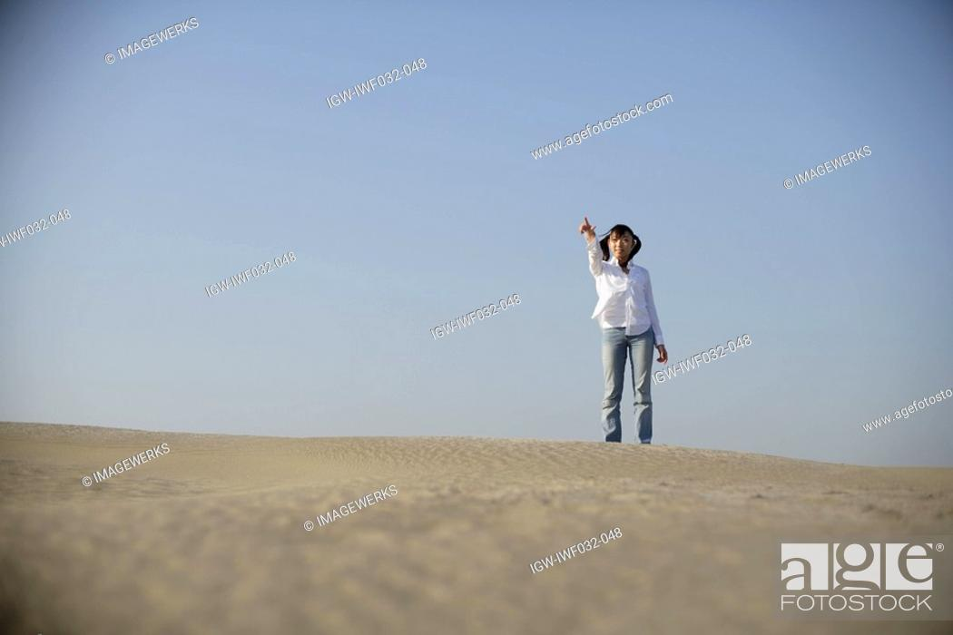 Stock Photo: Young woman standing alone in desert.