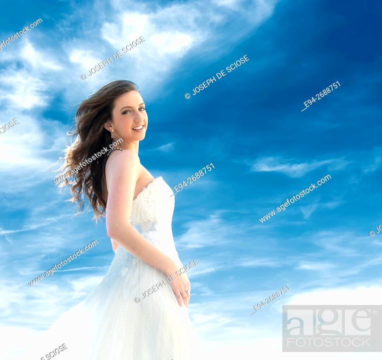 Stock Photo: A smiling young blond woman dressed as a bride in front of a blue sky with clouds. Memphis, Tennessee, USA.