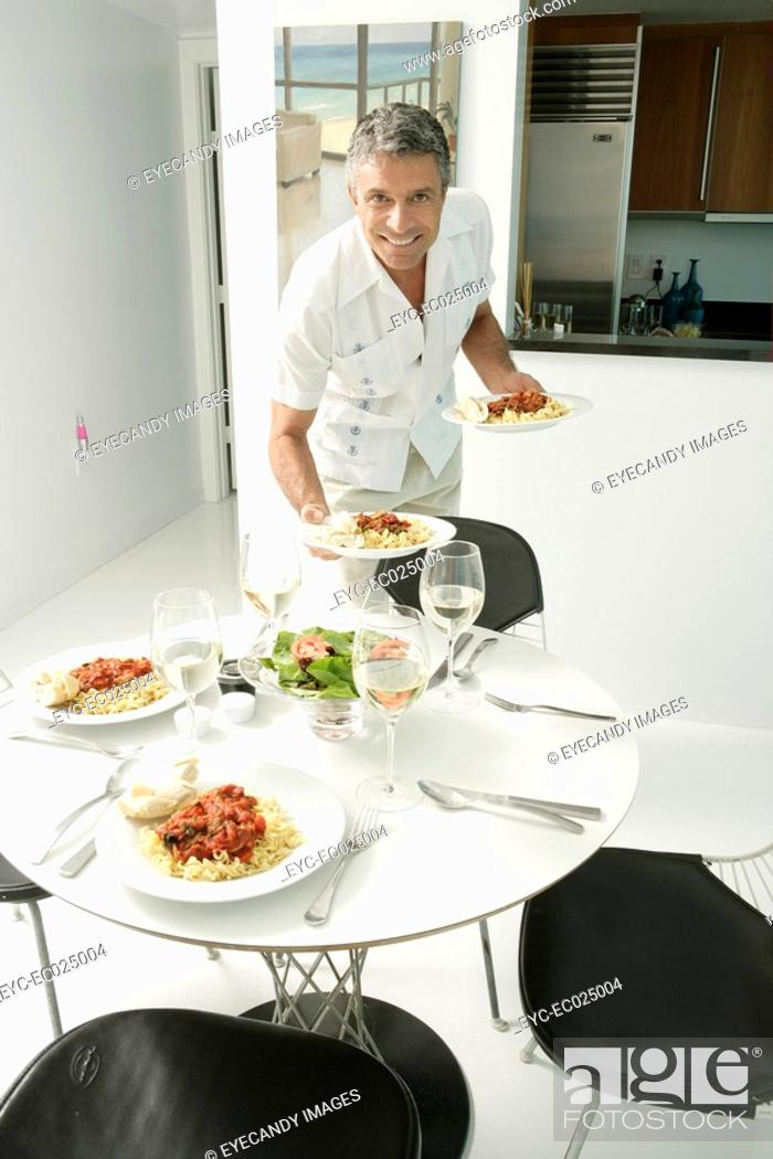Stock Photo: View of a man arranging dishes on a dining table.