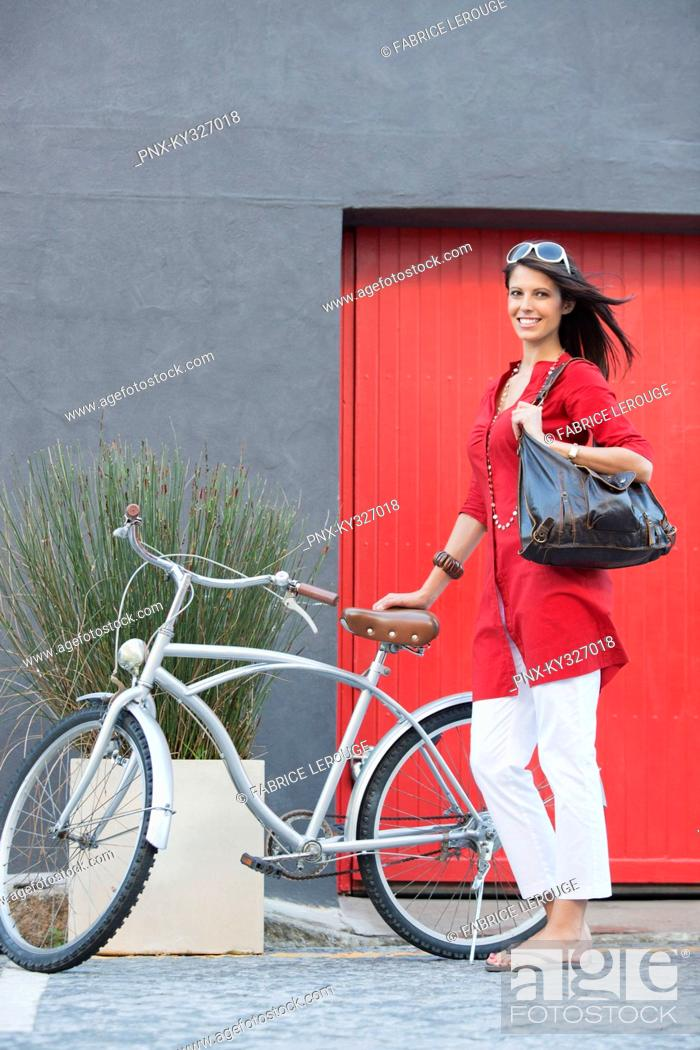 Stock Photo: Portrait of a young woman standing with a bicycle.