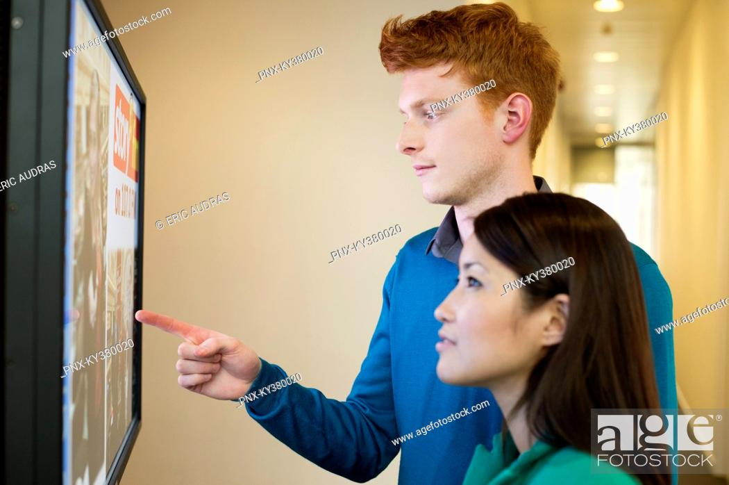 Stock Photo: Business people looking at display screen.