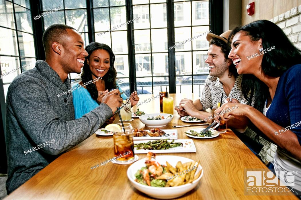 Stock Photo: Smiling friends enjoying food and cocktails at table in bar.
