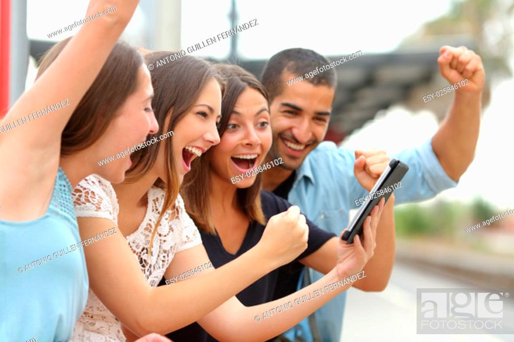 Stock Photo: Four euphoric multi ethnic caucasian and arab friends watching tv on a a tablet in a train station.