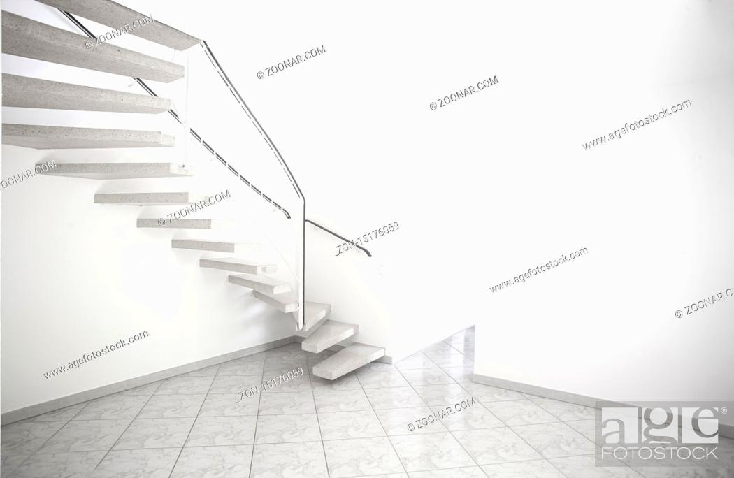 Imagen: twisted staircase in clean white building leading up to second floor with white walls and doors.