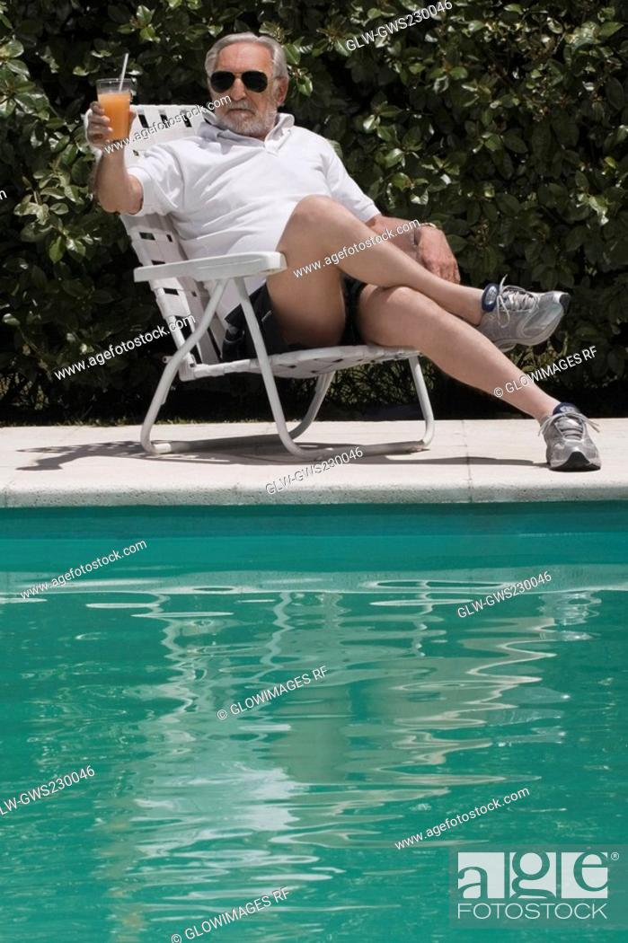 Stock Photo: Senior man sitting at the poolside and holding a glass of juice.