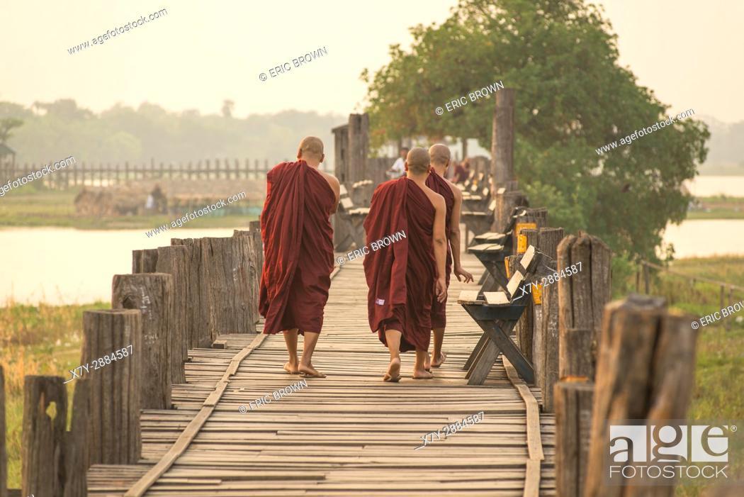 Stock Photo: Monks waking at sunrise over U Bein Teak Bridge, Amarapura, Myanmar.