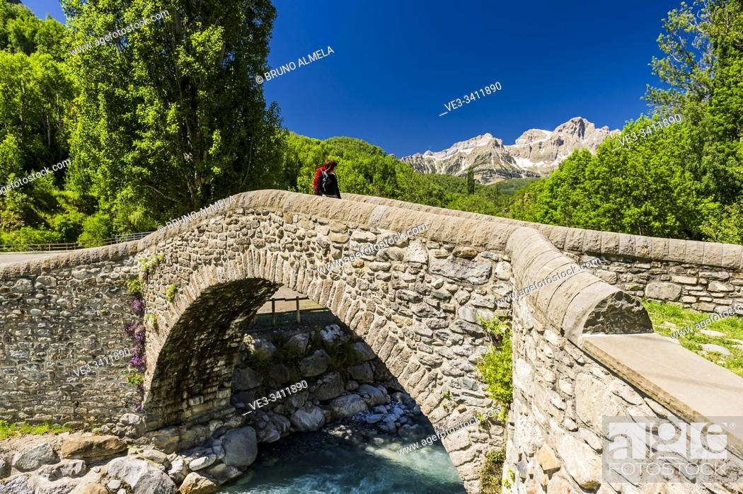 Imagen: Young hiker crossing the old bridge of Bolática River, Panticosa, Tena Valley, Pyrenees (Huesca province, Aragón, Spain).