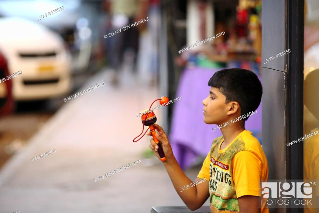 Stock Photo: Bangalore, India - October 16, 2016: Unknown kid sitting aside a shop spotted playing with his toy in Brigade Road, Bangalore.