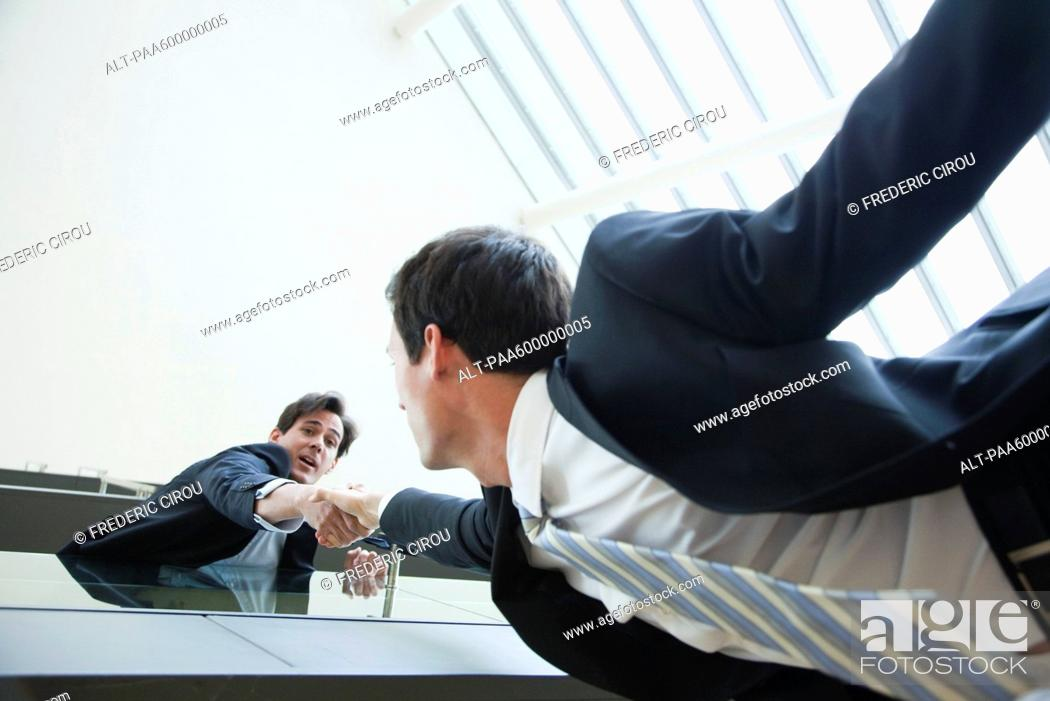 Stock Photo: Businessman leaning over balcony, holding on to colleague's hand.