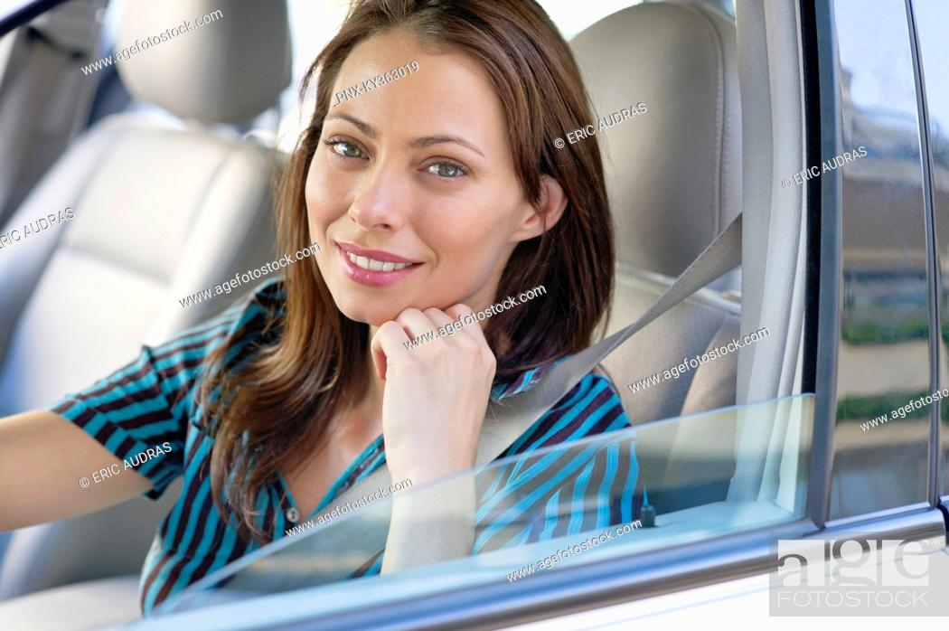 Stock Photo: Portrait of a beautiful young woman sitting at driver's seat.