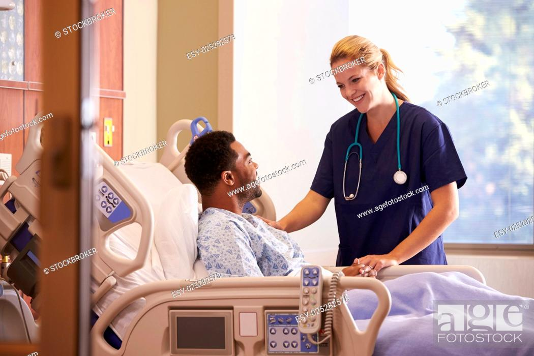 Stock Photo: Female Doctor Talking To Male Patient In Hospital Bed.